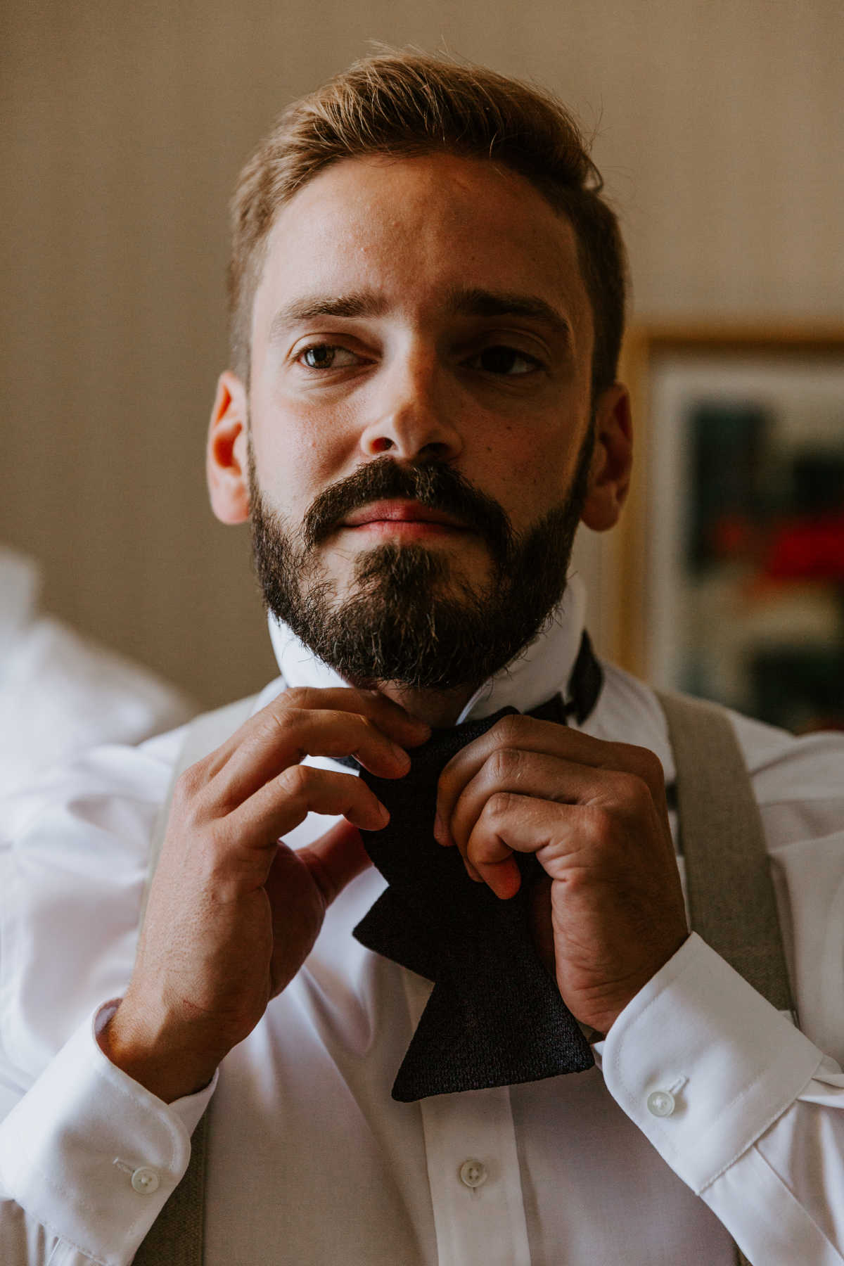 Close-up of the groom adjusting his bow tie