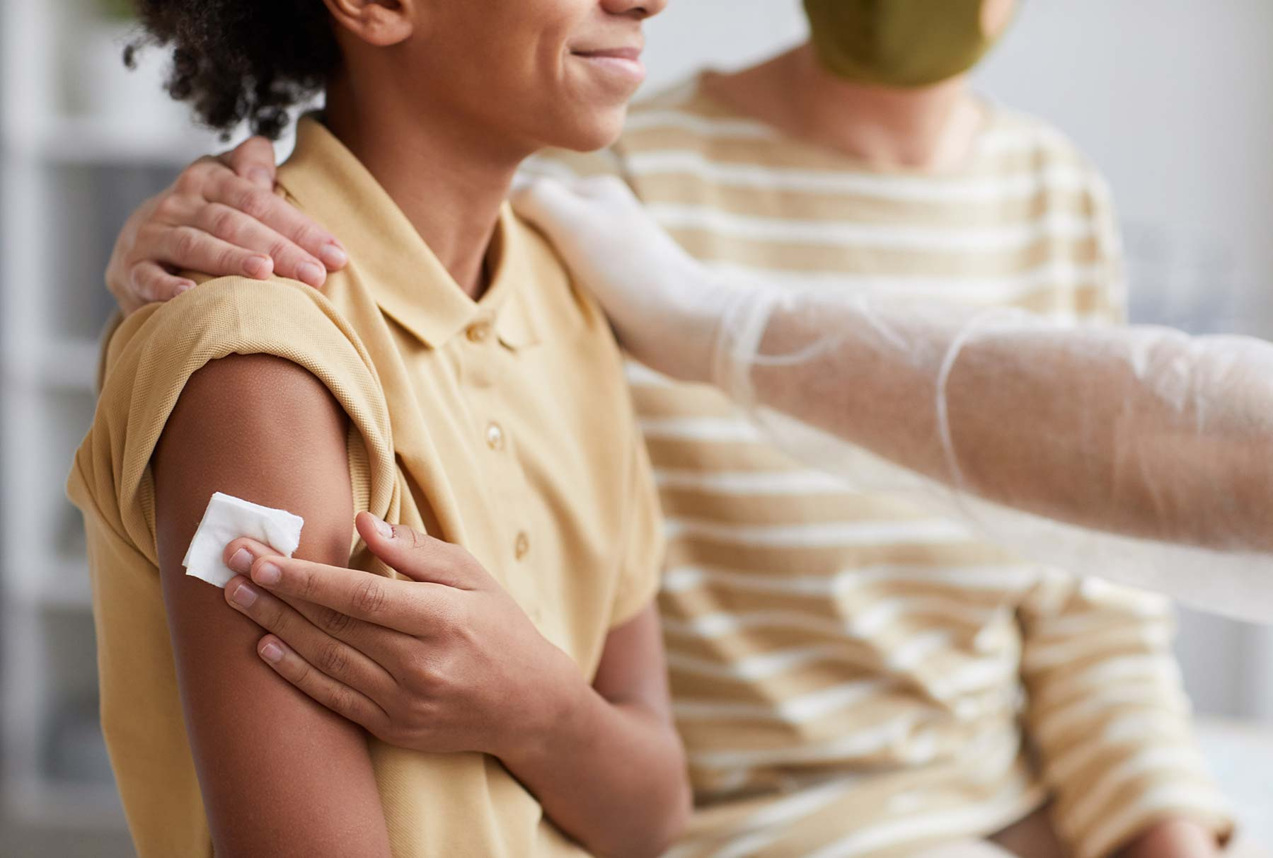 Young person who just received a vaccine shot, holding a swab to their arm and smiling.