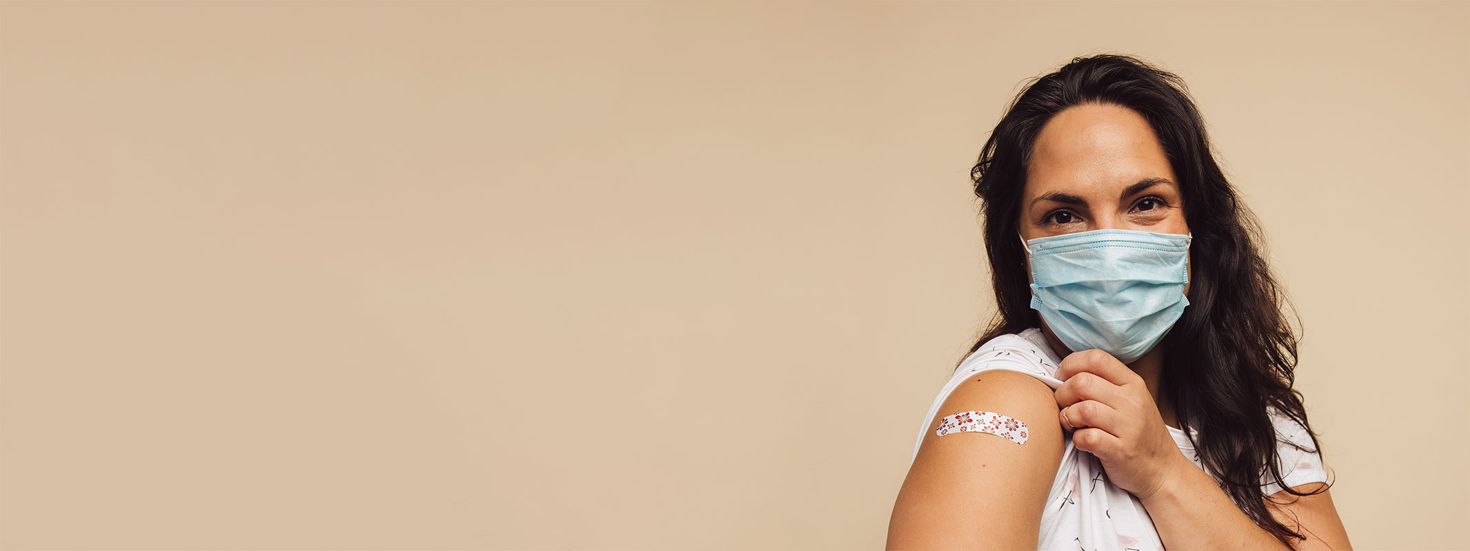 Woman happily showing off her bandaid from vaccination