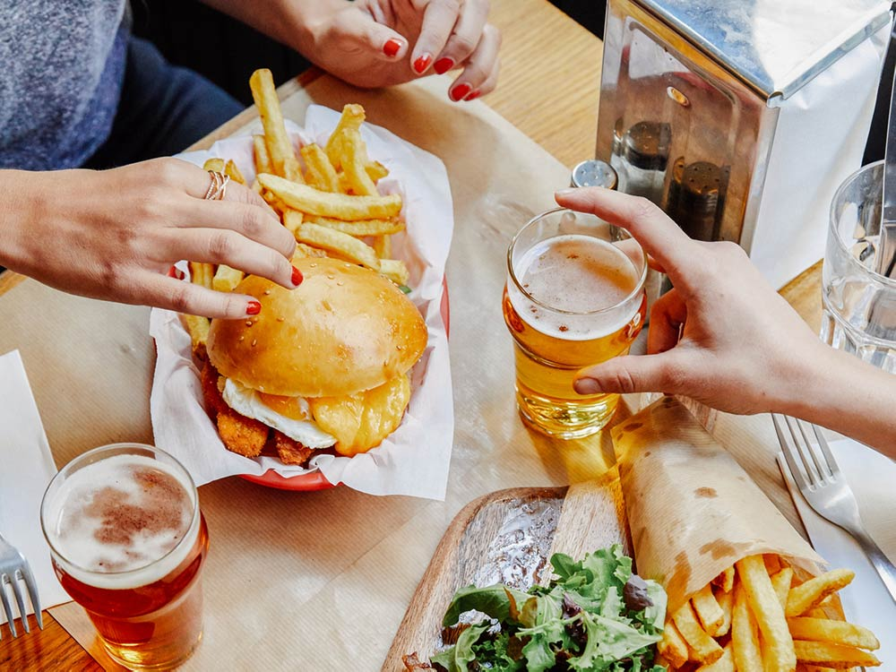 A tabletop setting with two people grabbing for their burger, fries, and beer