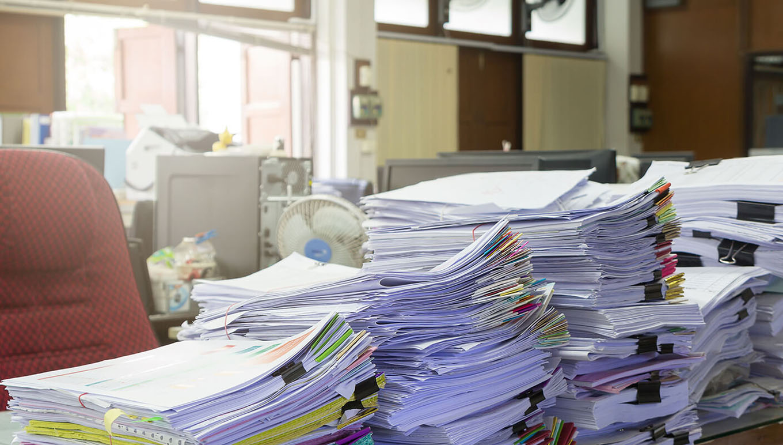 piles of paperwork on desk