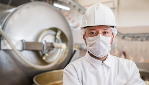 man wearing hardhat and mask in front of a manufacturing equipment
