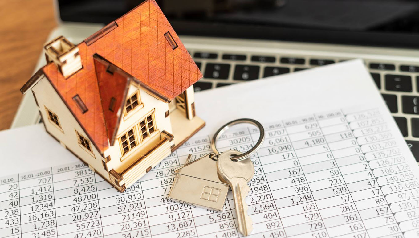 key and miniature house on mortgage spreadsheet