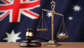 gavel and weight balance in front of Australian flag