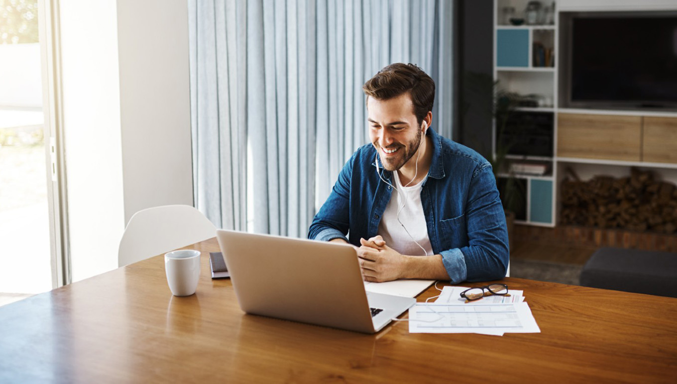 man at desk by laptop