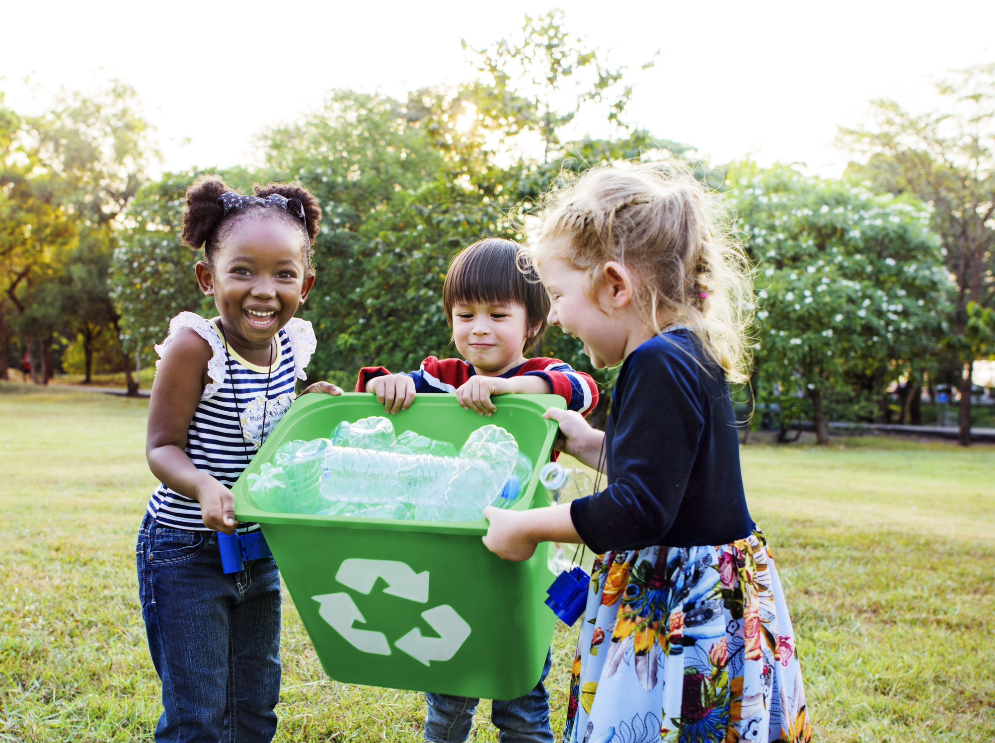 Three children laughing and holding a recycling bin.