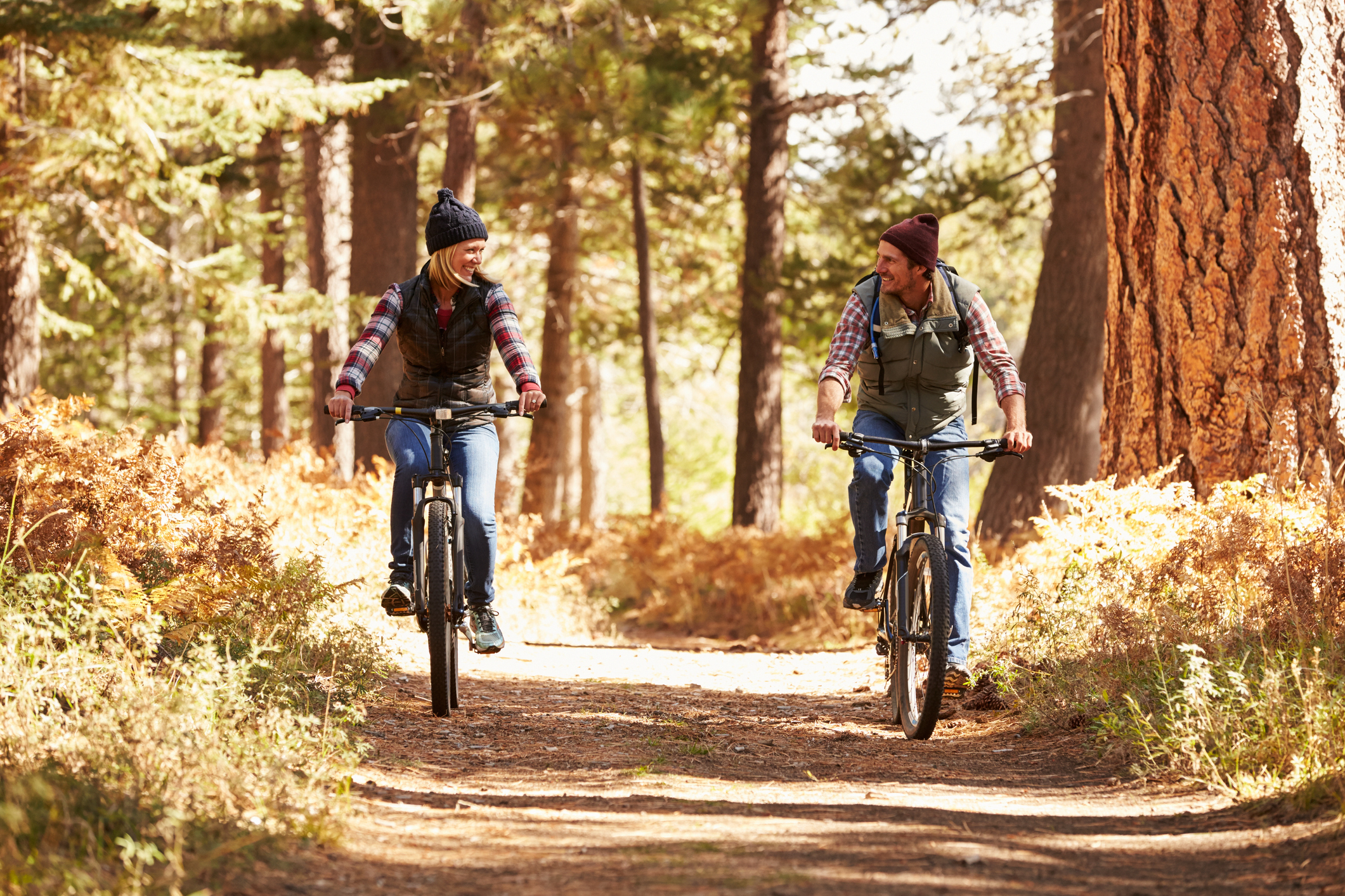 Two people social distancing while riding bikes in the fall.