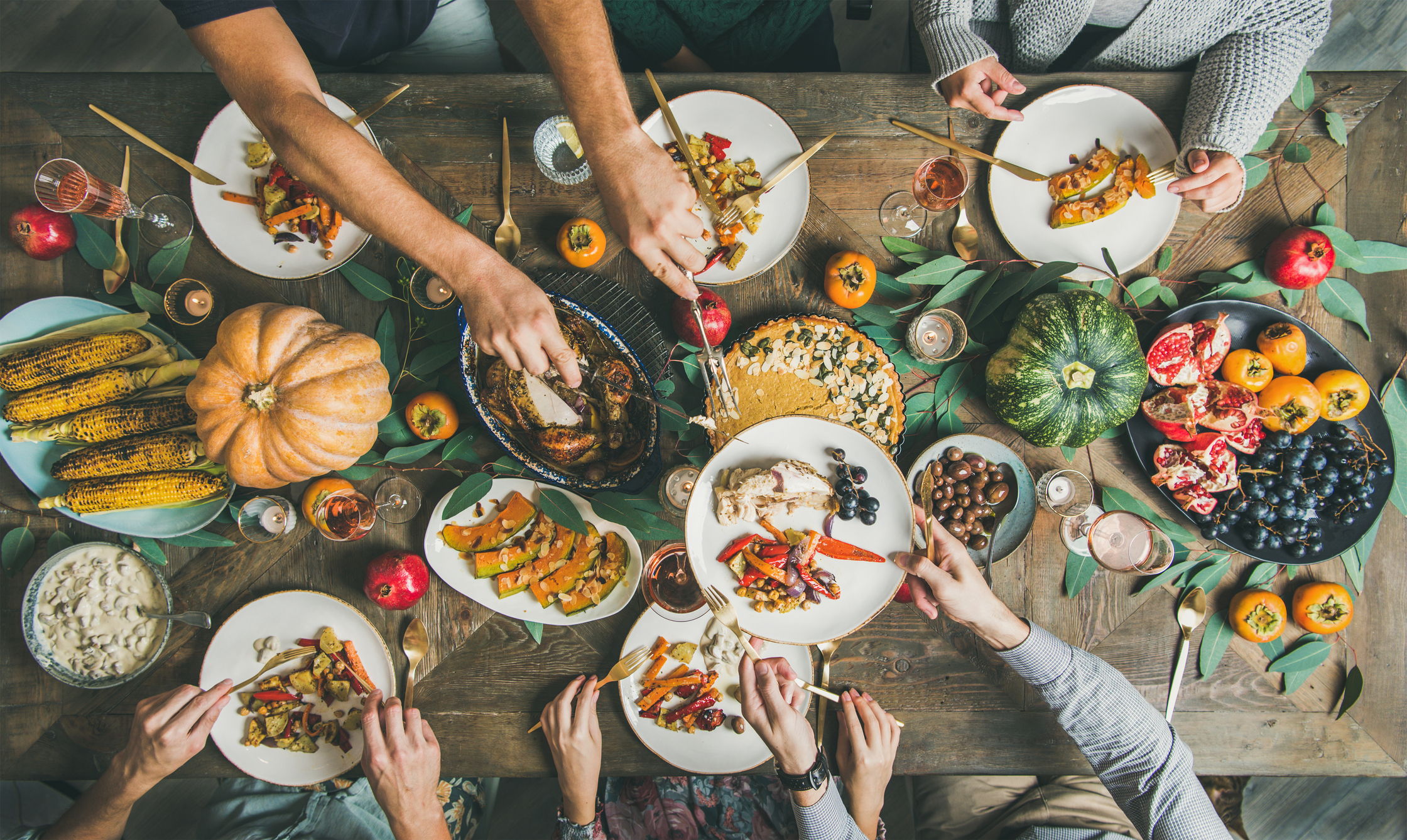 A group of people eating a vegan, plant-based Thanksgiving meal.