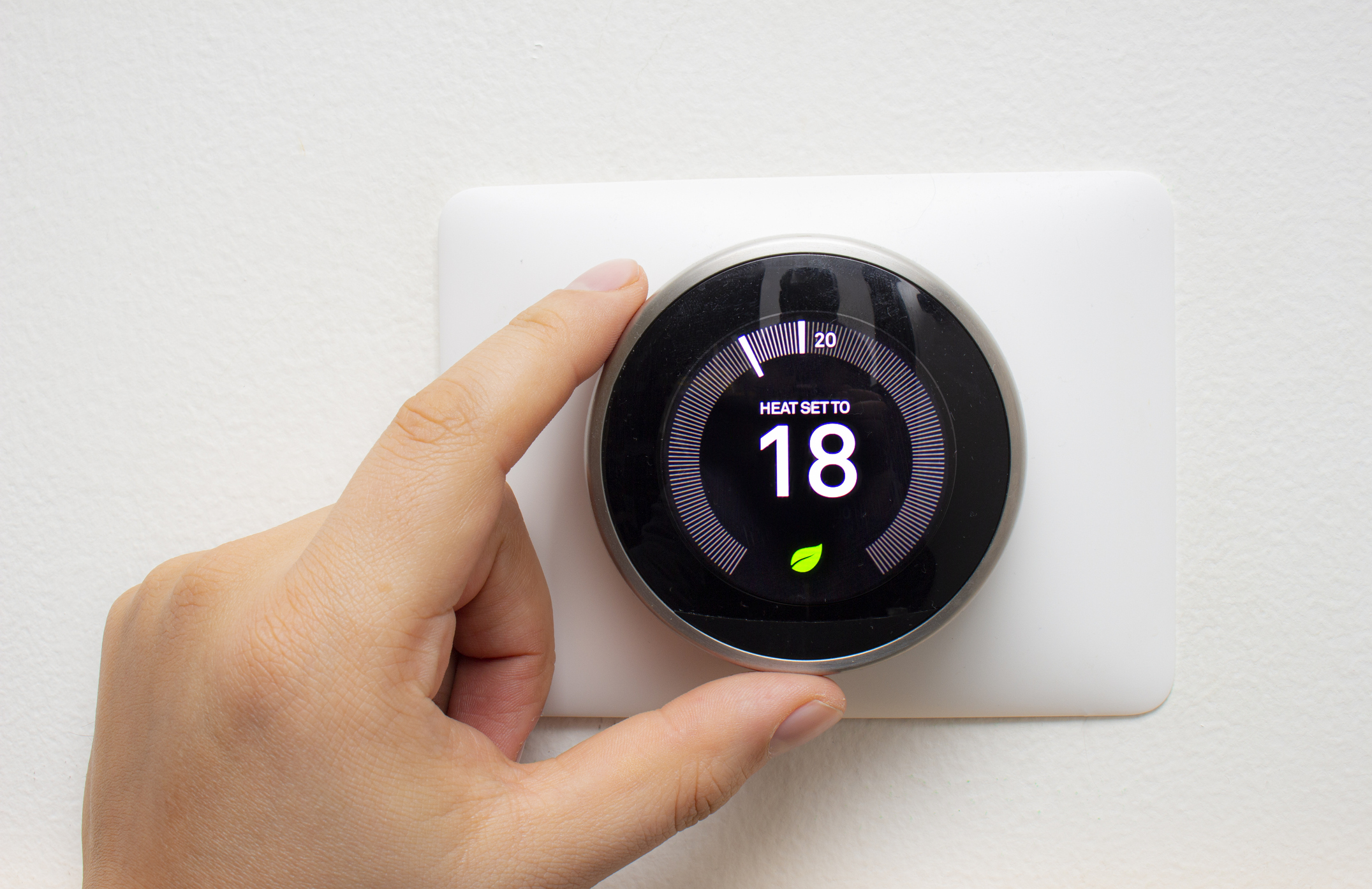 A person adjusting a smart thermostat in their home.