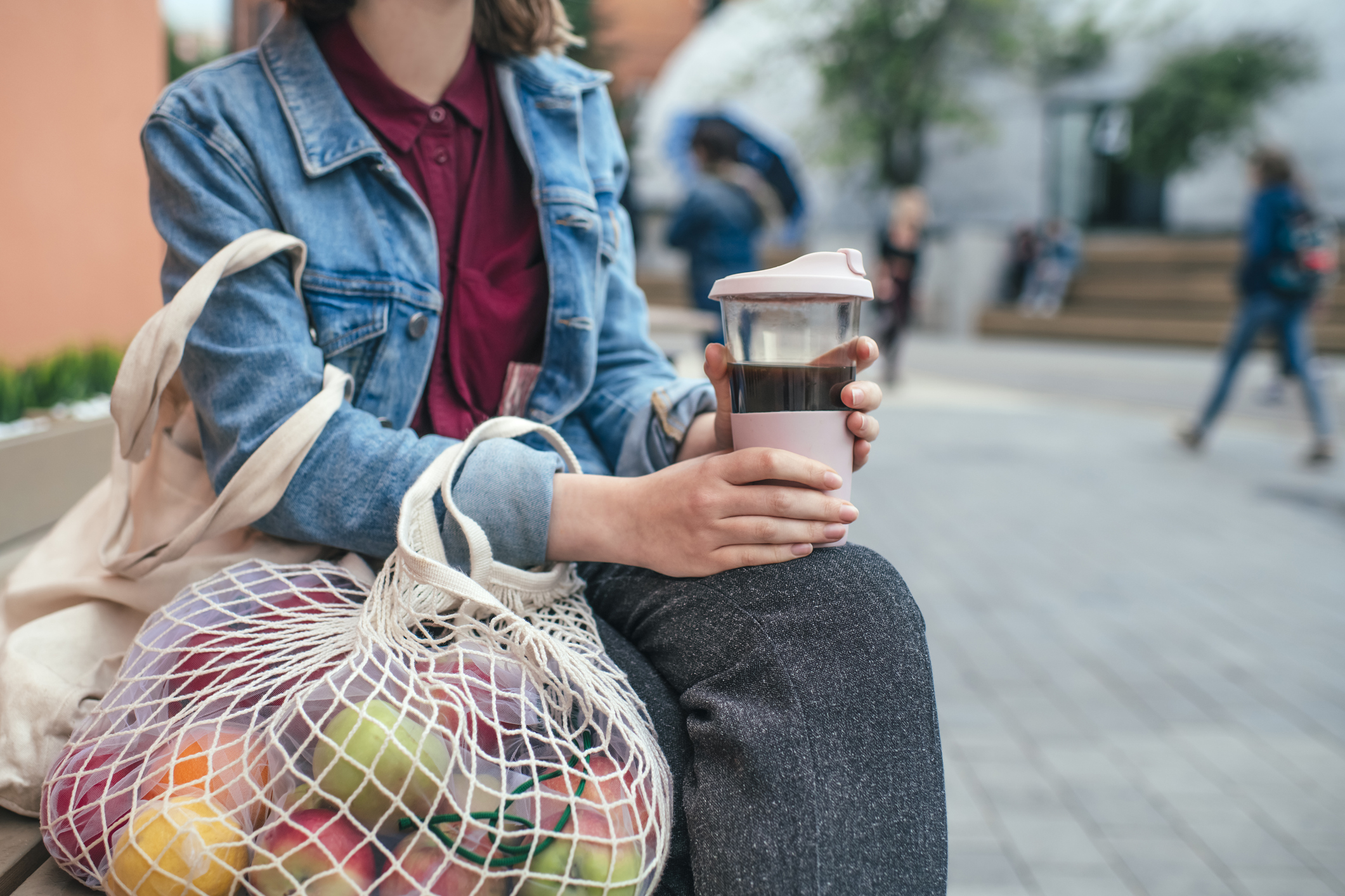 Woman holding a reusable coffee cup and mesh produce bag.