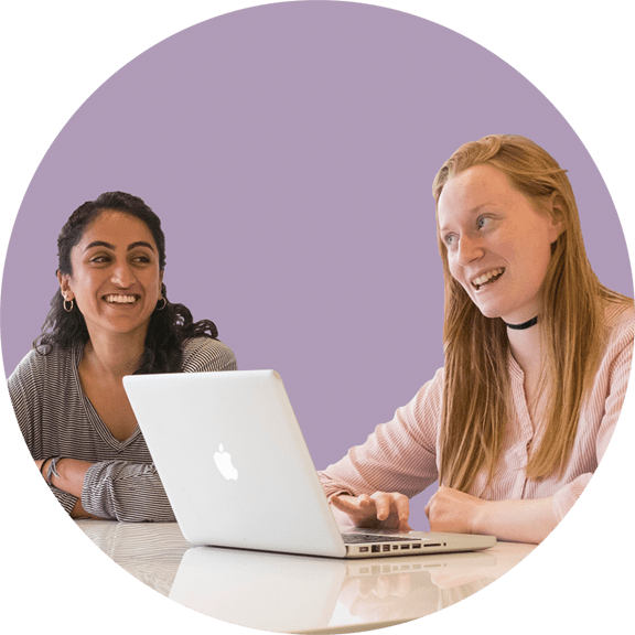 smiling black haired female tutor and blond female student using a laptop