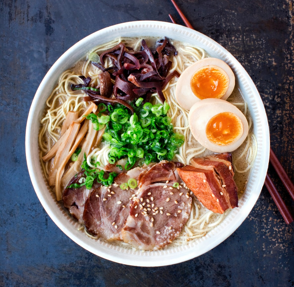 A bowl of ramen topped with egg, pork, green onion and bamboo shoots