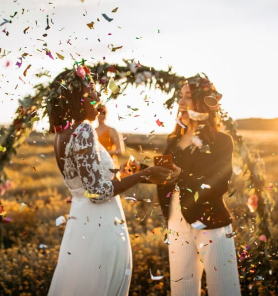 A Black woman and a White woman celebrate at an outdoor wedding in a field