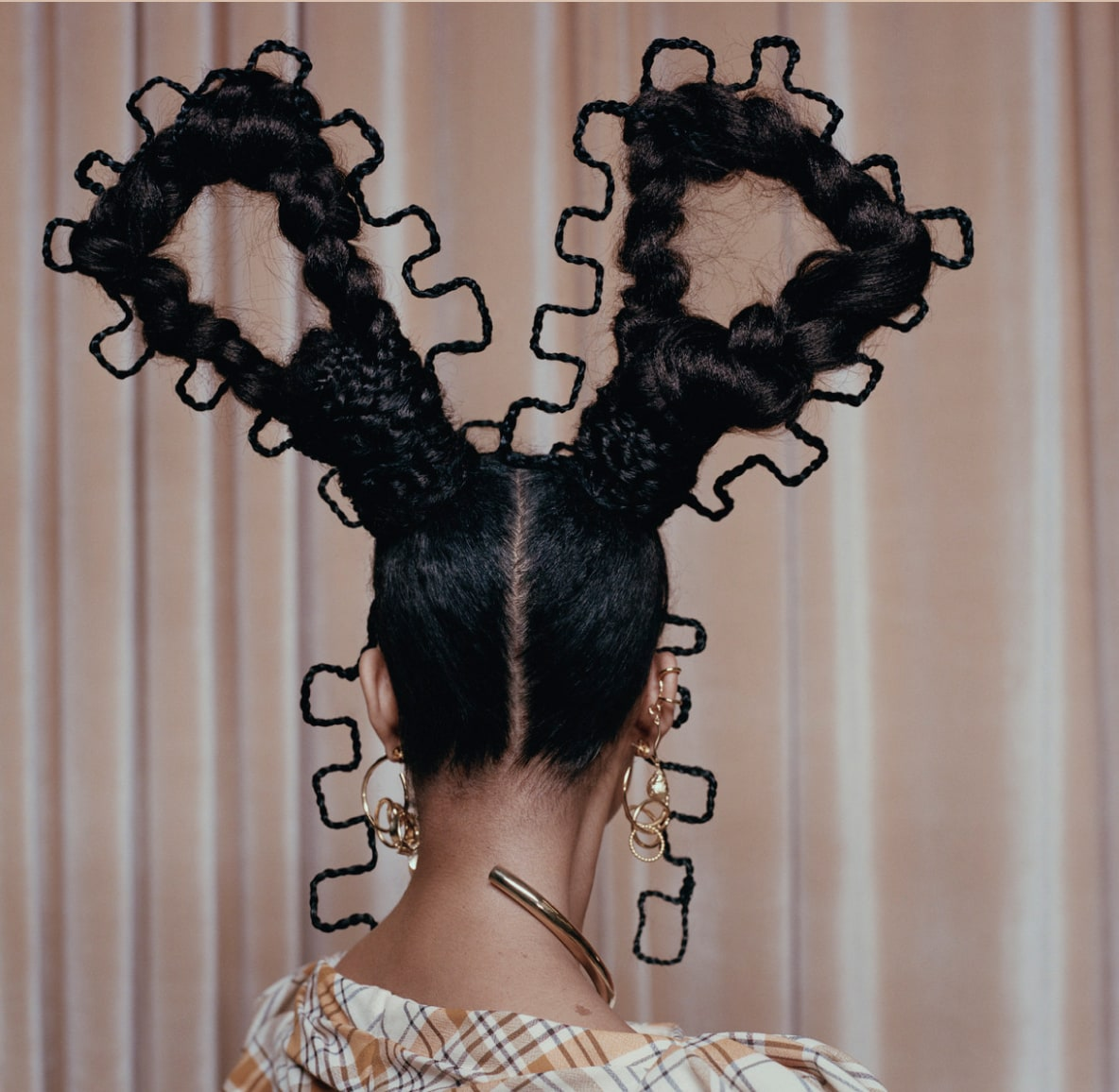 Back of woman's head with intricate, abstract braiding styles and a center part