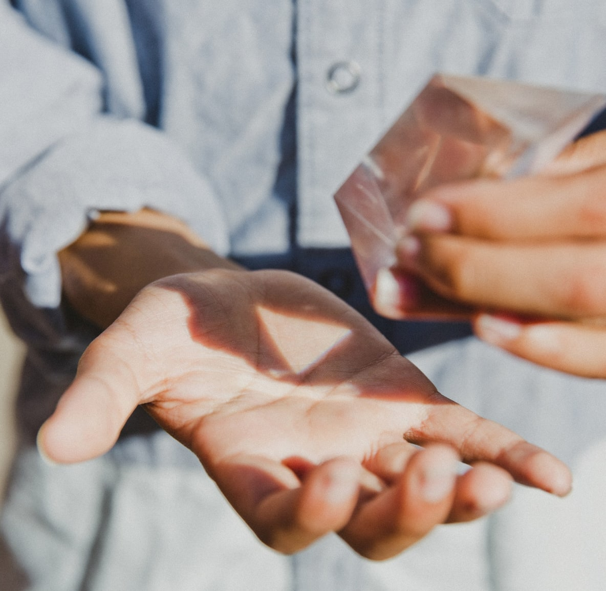 Woman holding a clear gemstone in her hands as it reflects in the sun