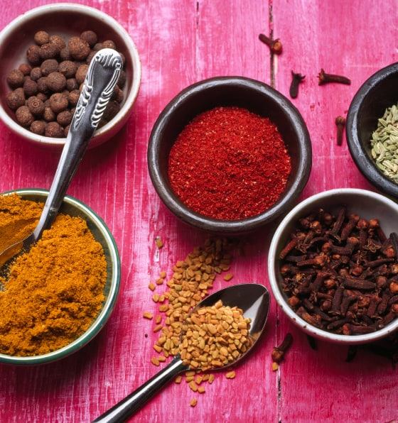 An array of red and brown spices in small individual bowls