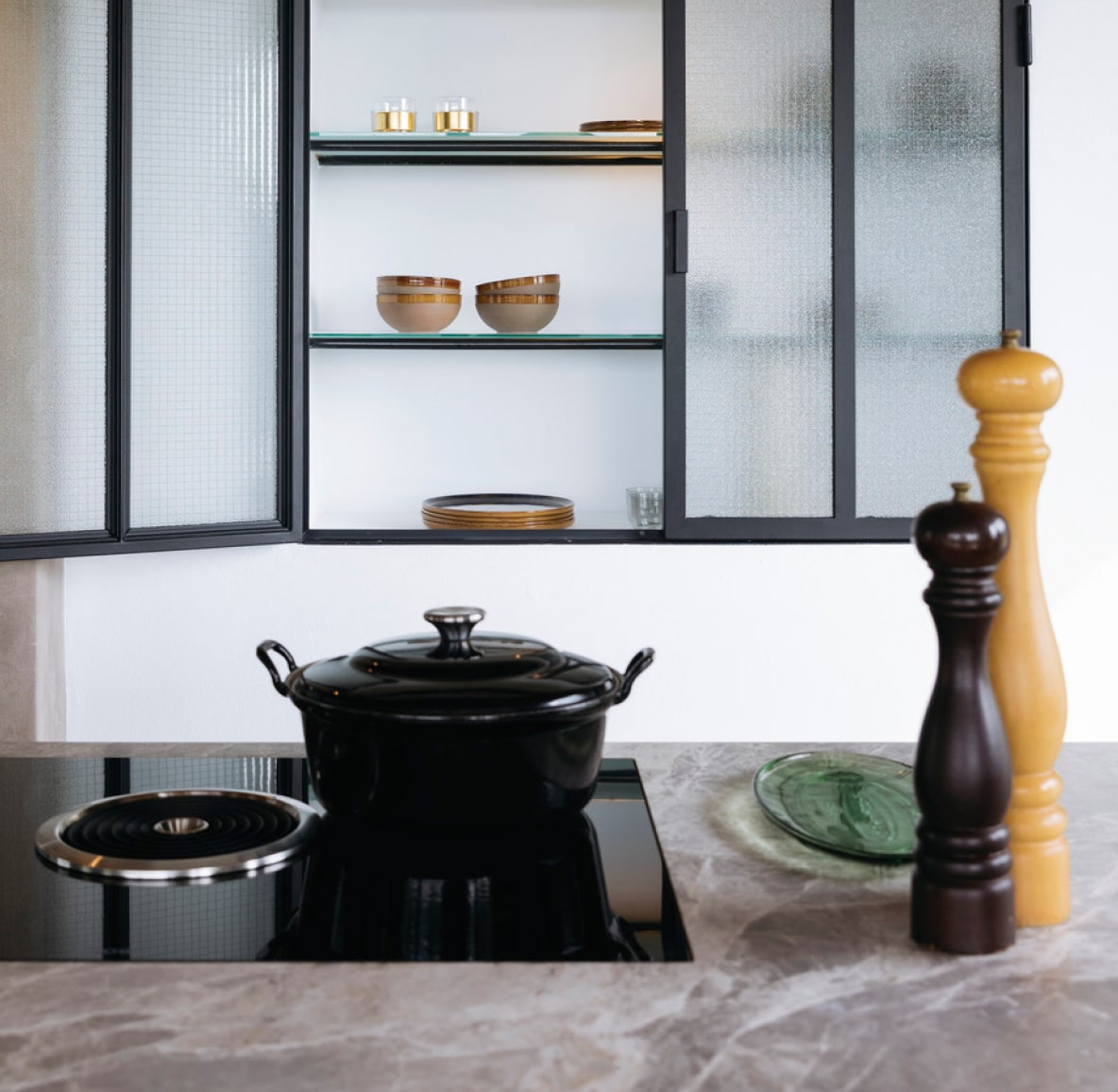 Kitchen countertop with ceramic cookware and large salt and pepper shakers in front of an open glass cabinet filled with ceramic dishes