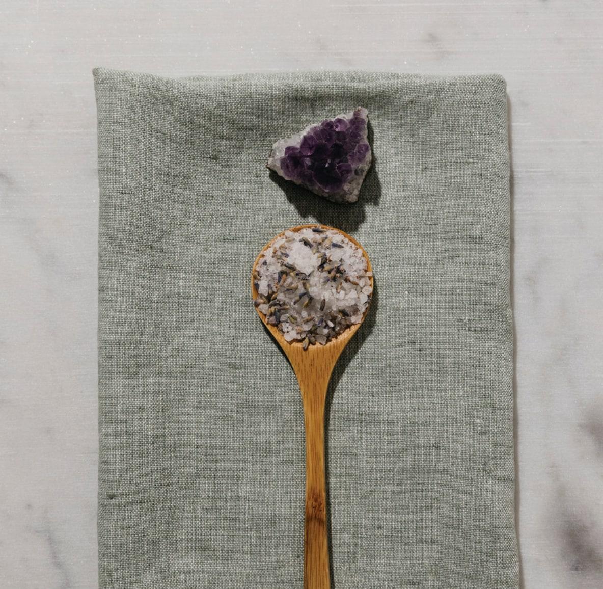Amethyst gemstone sitting next to a spoonful of lavender body scrub