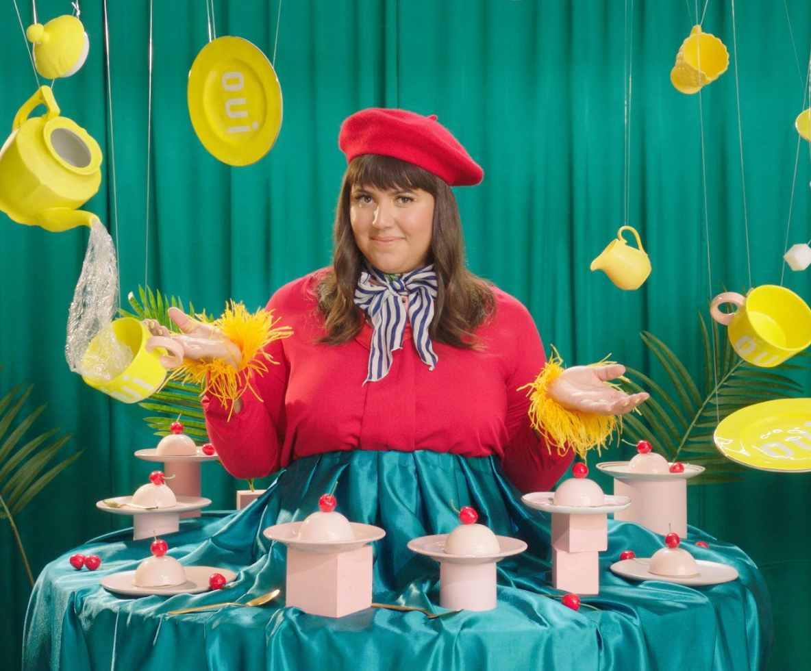 Raiza Costa displays pink confections on a boldly colored set