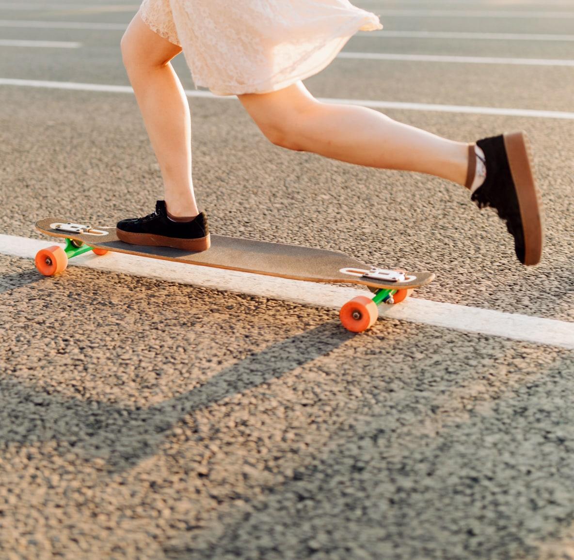 Woman wearing a skirt riding a skateboard