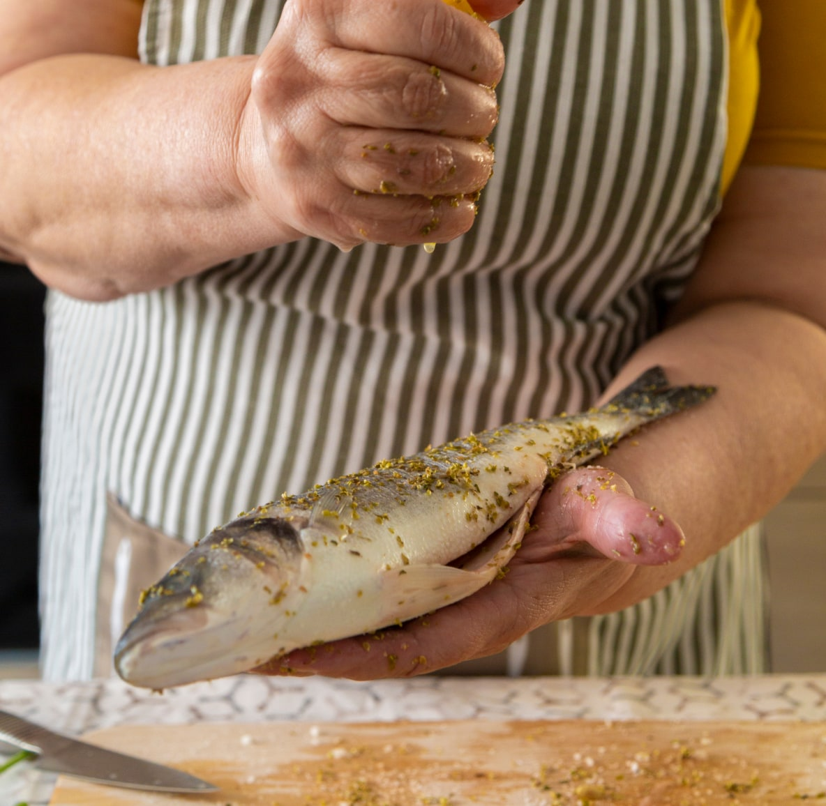 Woman in a striped apron seasoning a whole fish with her hands