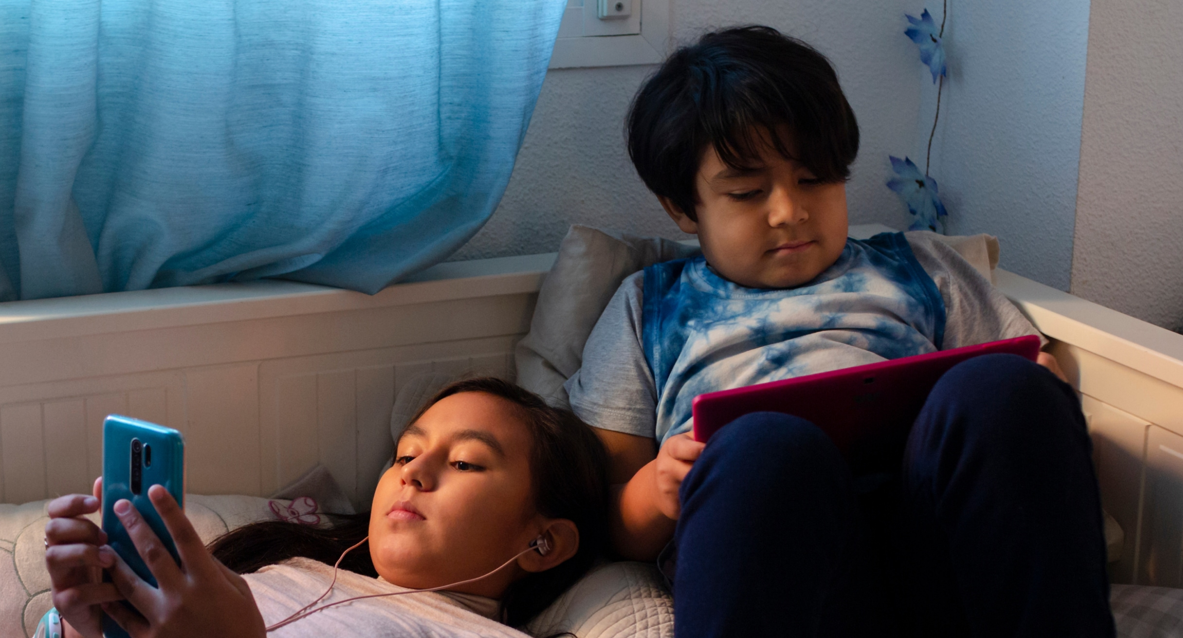A Latinx girl and boy lounge on a bed with their mobile devices in hand