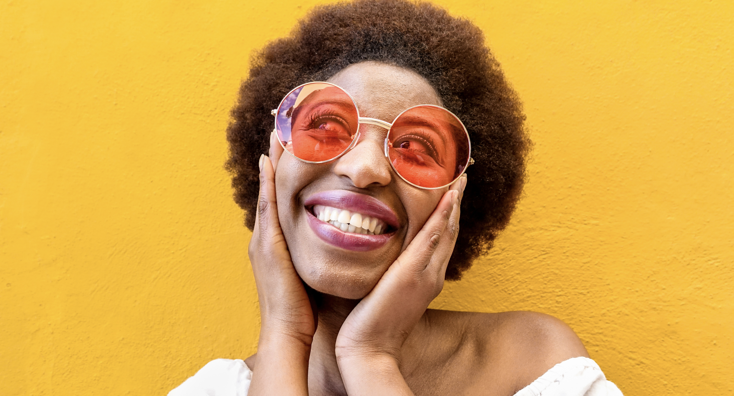 A Black woman in large, tinted glasses smiles and holds her cheeks in front of a yellow wall