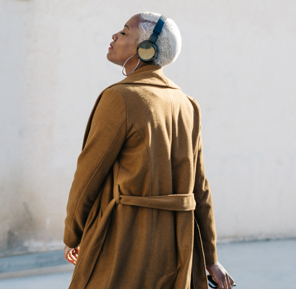 A Black woman with short white hair in a Brown trenchcoat and wireless headphones