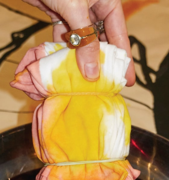 Closeup shot of hands tie-dying white fabric with yellow and pink dye