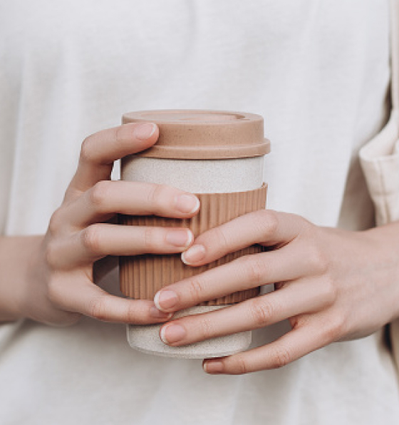 White hands hold a recyclable to-go coffee cup