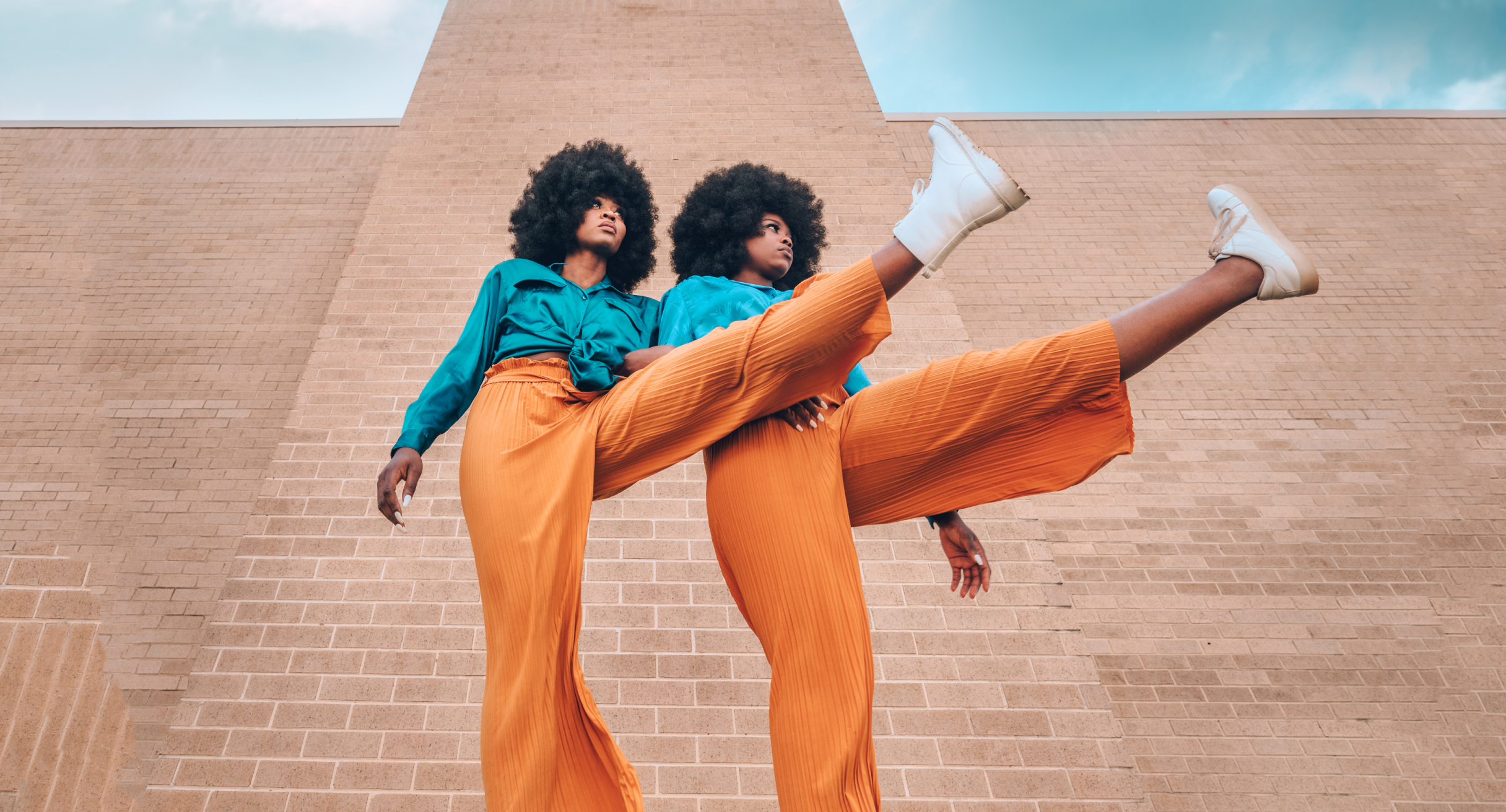 Two women in matching outfits kicking up their legs