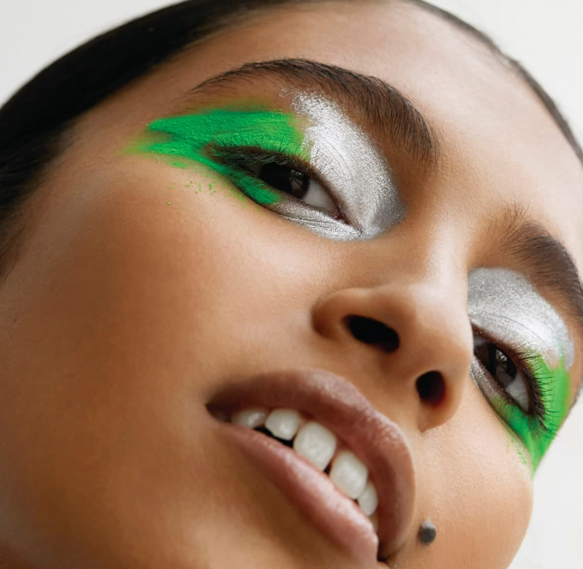 Young woman looking into the camera with dramatic electric green and silver eyeshadow