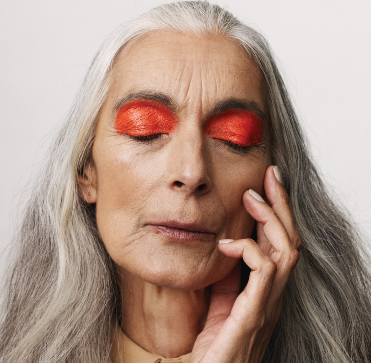 Woman with gray hair wearing no makeup except for bright orange eyeshadow