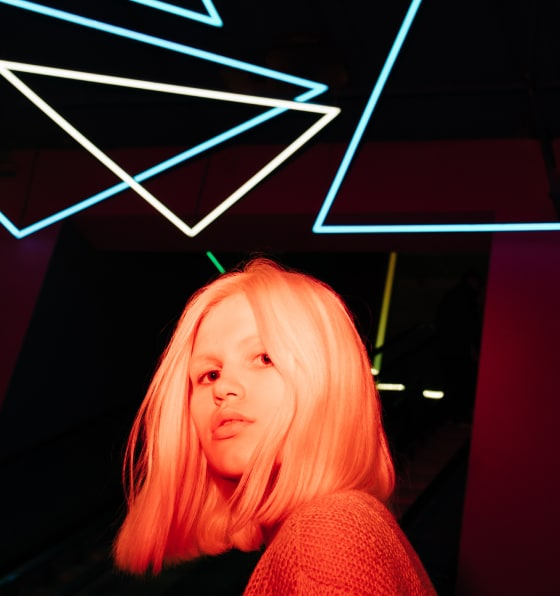 Teenage girl with short blonde hair standing in front of neon triangle lights