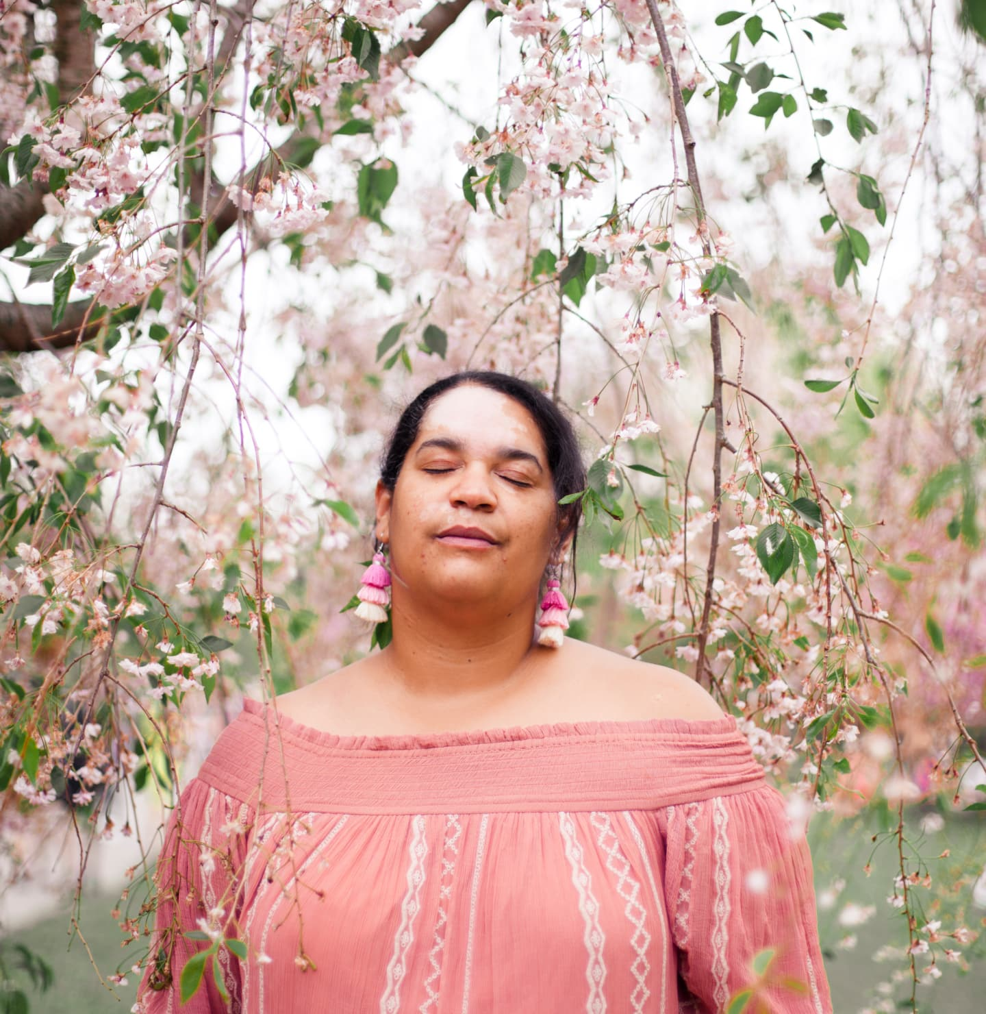 A Black woman in pink stands with her eyes closed under the white and pink blossoms of a tree