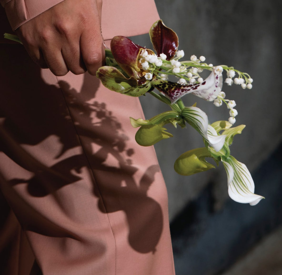 A person in a pink suit holding a simple stem of orchids