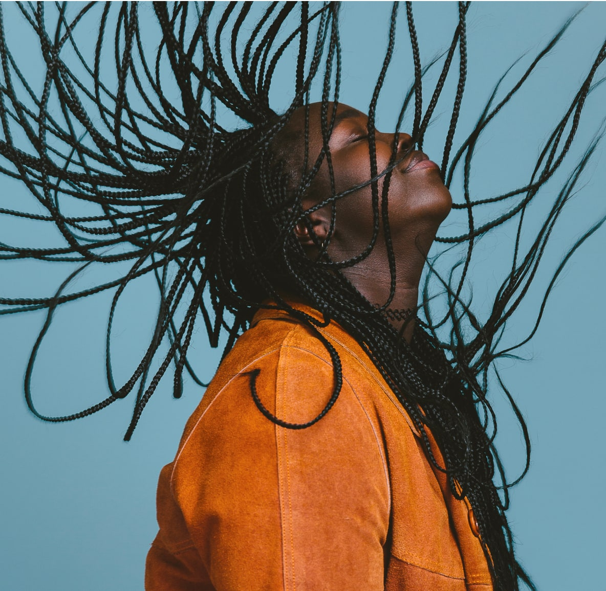 Profile shot of a woman in motion with protective braids spread out around her face.