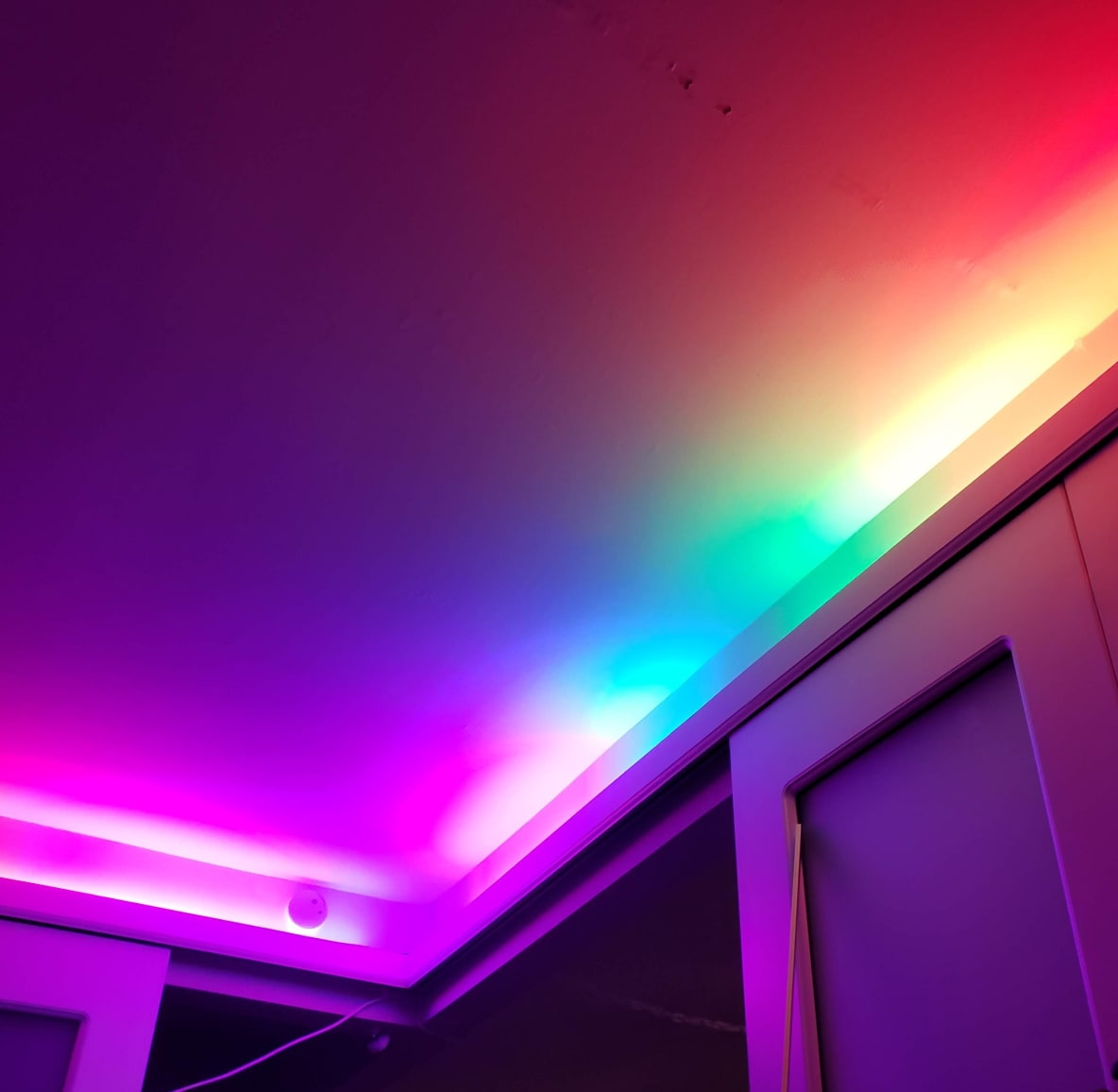 Rainbow strip of LED lights lining the walls of a bedroom