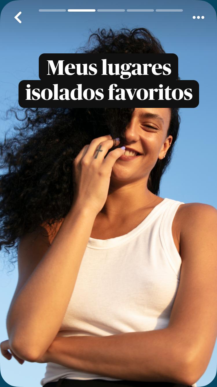 Uma mulher mediterrânea sorri, seu longo cabelo preto cobre metade do rosto, com o céu azul ao fundo e uma sobreposição de texto: Meus lugares isolados favoritos