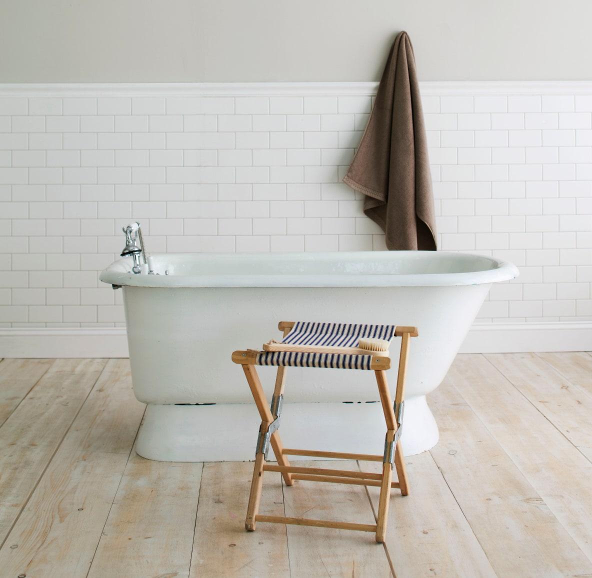 Free-standing bathtub next to folding chair and brown hanging towel