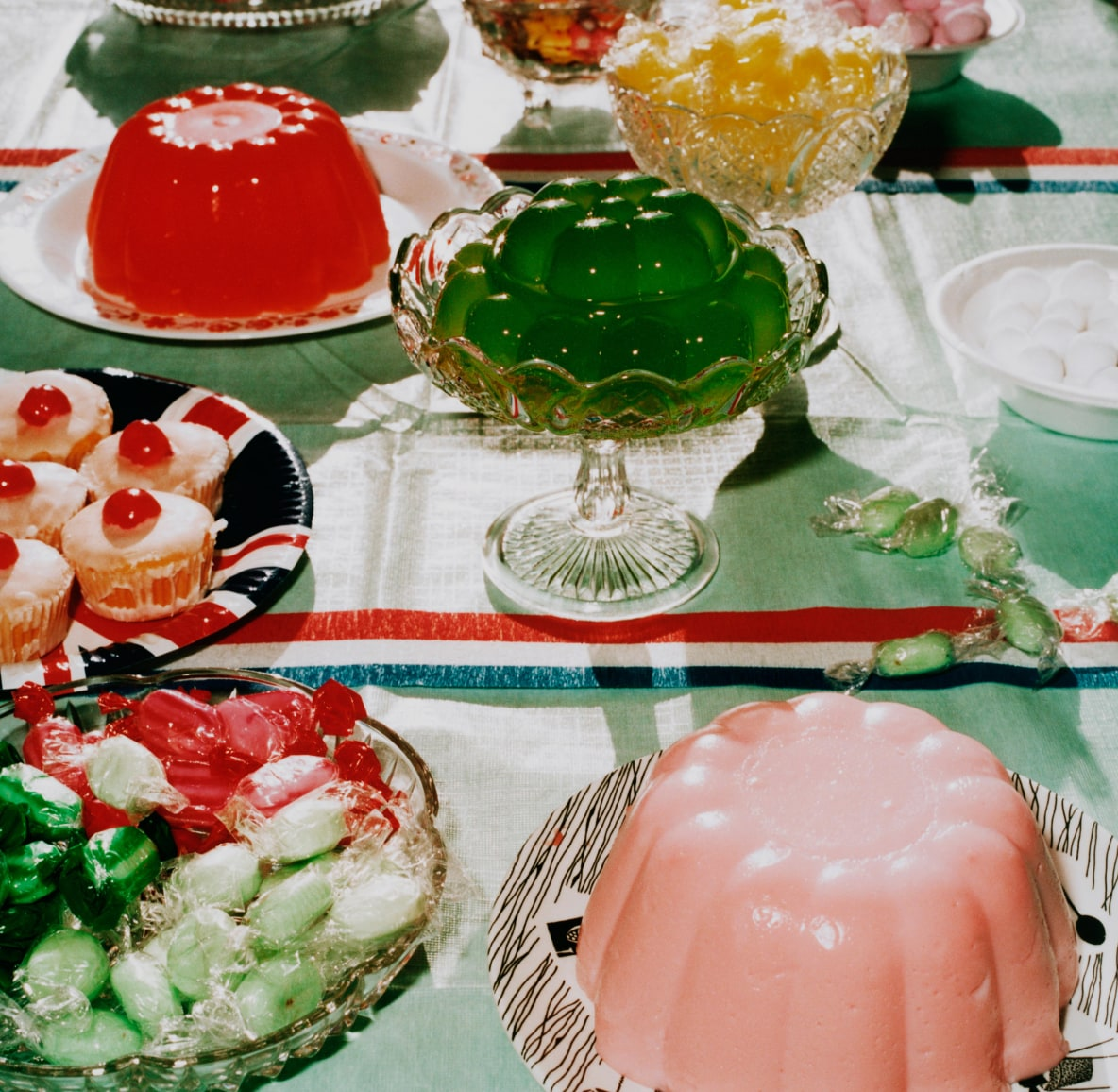 Tablescape featuring colored gelatin molds, cupcakes and candy