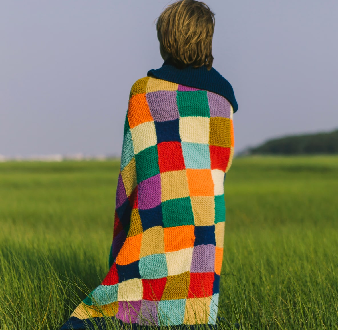Image of person in a field wrapped in a brightly colored checkered blanket