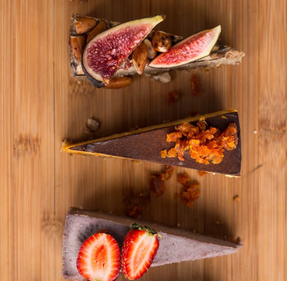 Três fatias de tortas de frutas diferentes exibidas ordenadamente em uma tábua de madeira