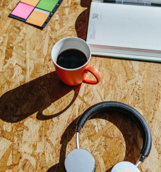 A wood table with orange coffee cup, over-ear headphones, datebook, and an assortment of post-it notes