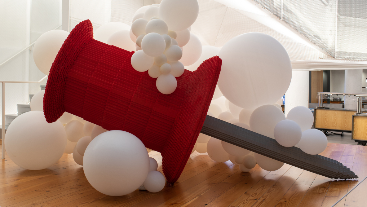 A gigantic red Pin replica among large white balloons in the Pinterest headquarters lobby