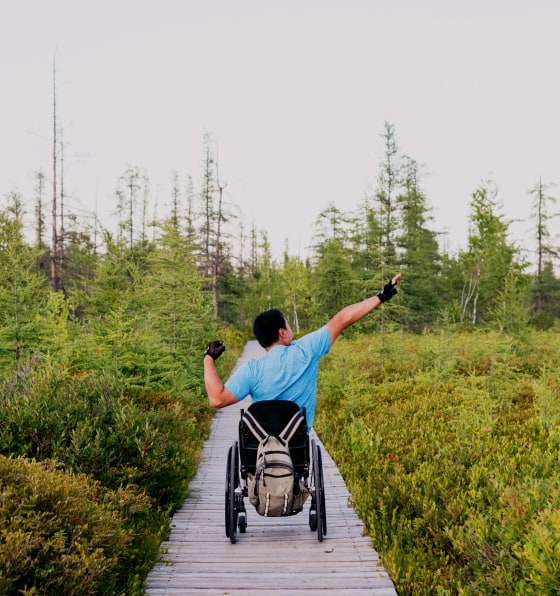 A man in a wheelchair on a paved path among trees