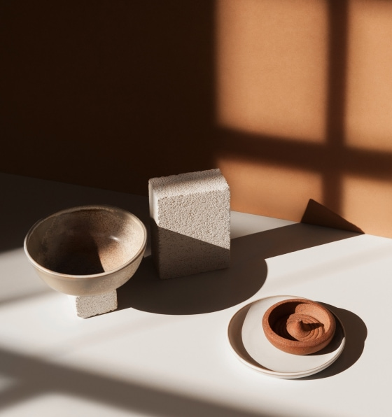 Ceramic bowls and a small block of cinder staged in moody lighting