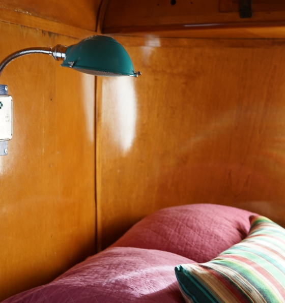A small camper room with finished wood walls, green wall lamp, and multicolored pillows