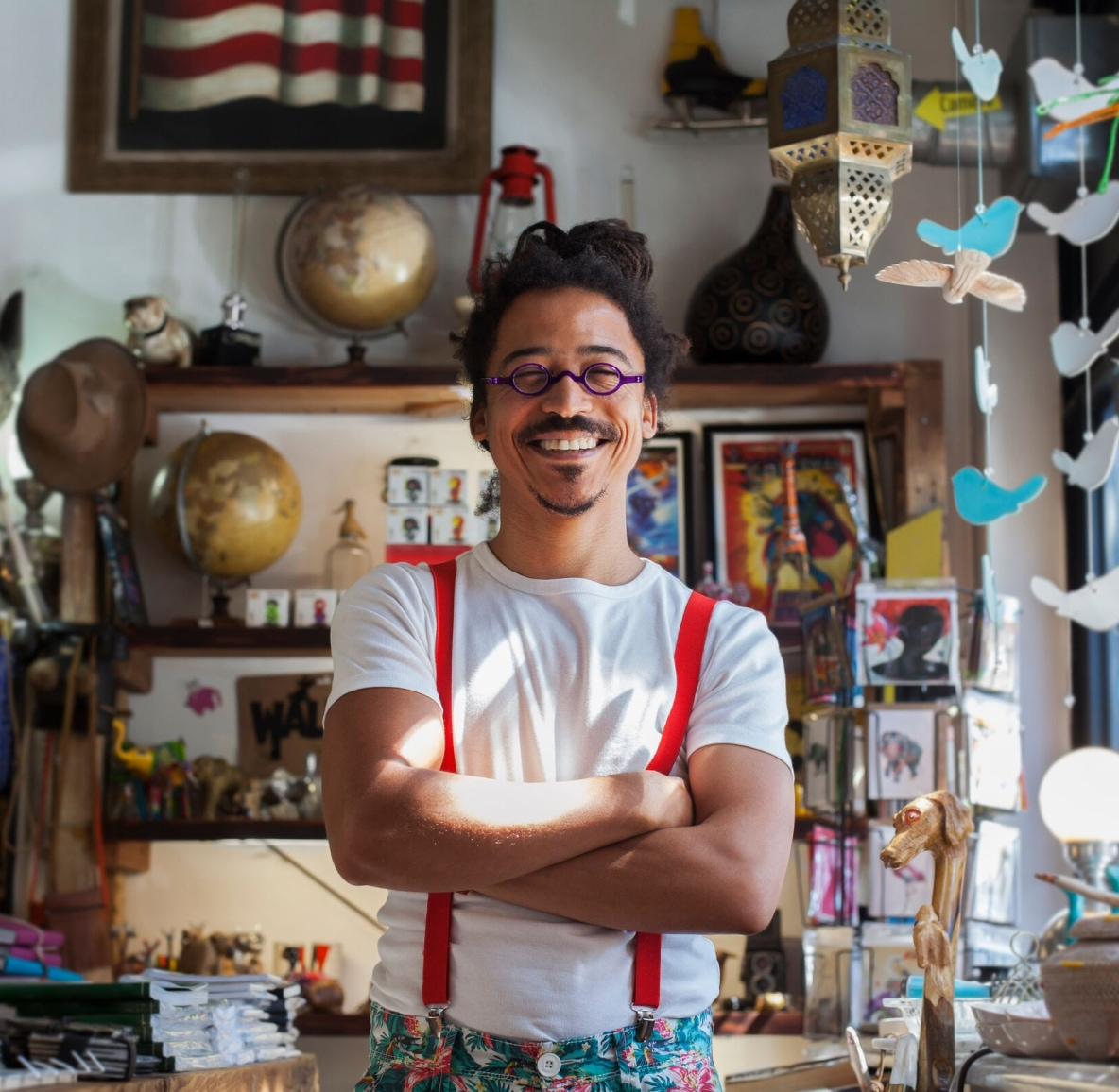 A smiling Black man with locs and red suspenders stands in a curio shop, arms crossed