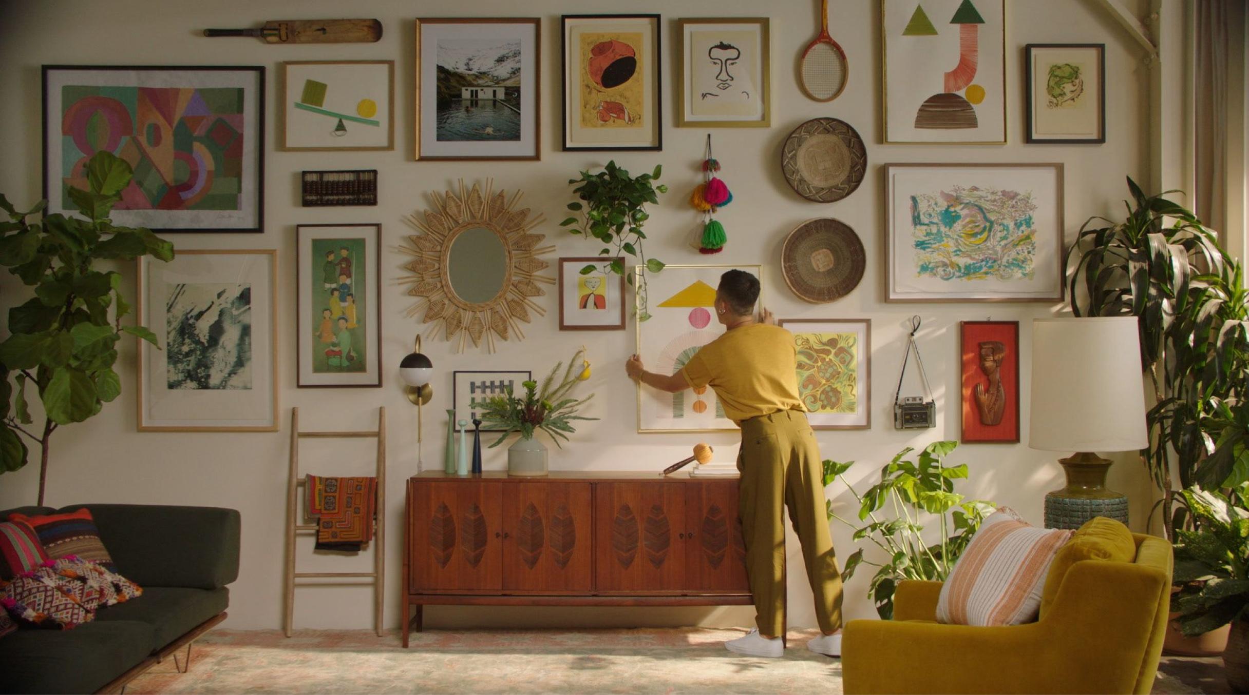 Dabito hangs art on his gallery wall